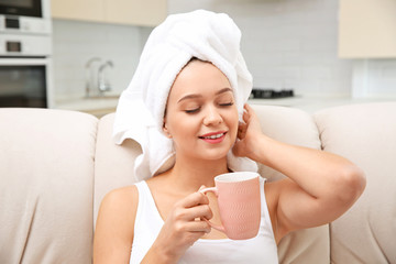 Beautiful woman with hair wrapped in towel sitting on sofa and drinking tea at home