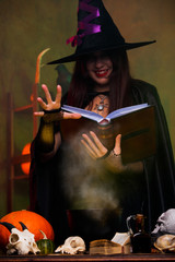 Photo of witch in black hat and with black book brewing potion