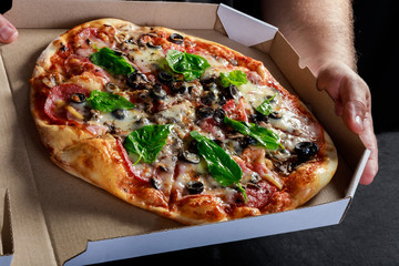 Pizza box delivery concept. Open box with hot tasty italian sliced pizza with olives, basil, tomato, mushrooms.