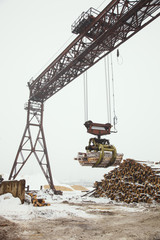 Heavy lifting crane for loading of harvested wooden logs.