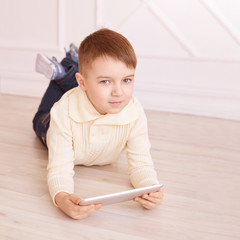 Cute boy. Computer tablet. play game, chat. Training. light interior