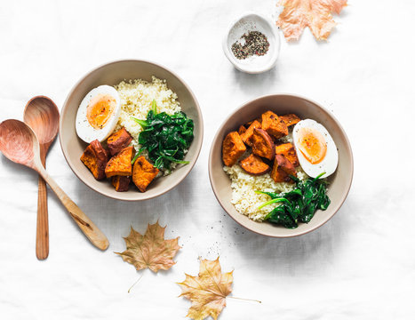 Sweet potato, couscous, spinach, egg buddha bowl on light background, top view. Vegetarian food concept