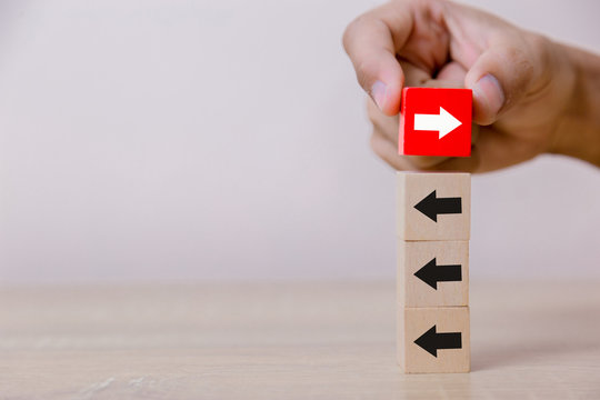 Hand putting wood cube block on top vertical red wooden blocks with white arrows facing opposite to the black arrows. With different concepts to other people. Going for success.