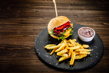 Tasty burger with chips served on black stone on wooden background