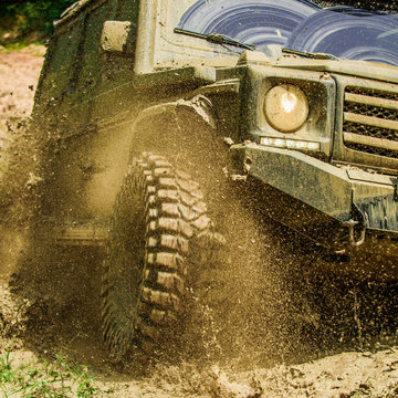 Off-road travel on mountain road. Travel concept with big 4x4 car. Mud and water splash in off-road racing. Motion and power concept.