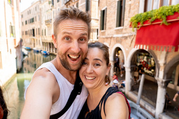 Sweet couple in love taking a selfie in Venice Italy while traveling around europ