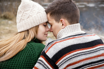 Couple in love having fun outdoors at picnic. Leisure activities, caucasian young girlfriend and boyfriend, lovers resting near river. Stylish hipsters, wearing cute trendy outfit, smiling enjoy