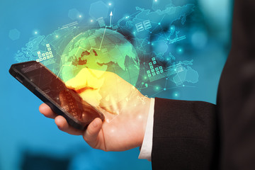 Hand using phone with global reports and stock market change concept