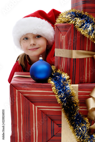 b53b8086a Cute little girl in a Santa Claus cap with Christmas gifts, isolated ...