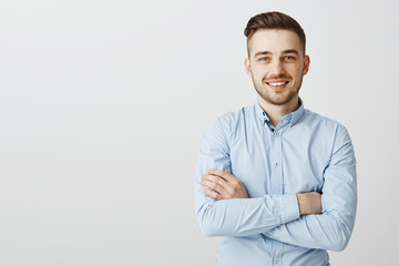 Confident and friendly handsome ambitious man with bristle in blue collar shirt holding hands crossed on chest in self-assured pose smiling joyfully intirigued to listen new idea how gain clients