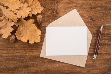 Envelope with a pen and autumn leaves