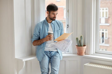 Serious businessman reads text of contract, analyzes documentation, concentrated on financial information, wears denim clothes, stands near window for good vision, drinks hot aromatic beverage