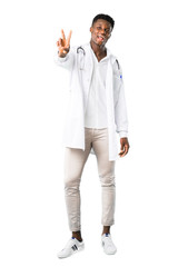 Full body of African american doctor smiling and showing victory sign on white background