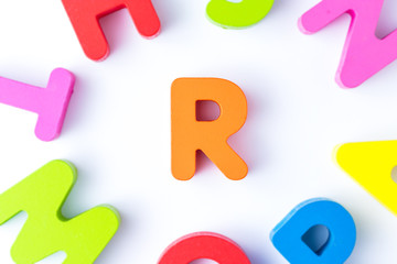 R letters in English made from wood bright colors.