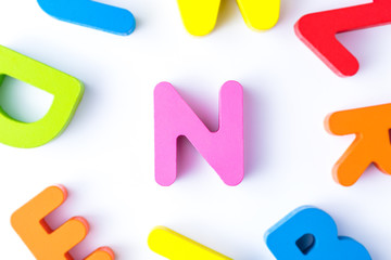 N letters in English made from wood bright colors.