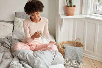 Joyful female blogger enjoys recreation time, does shopping online, uses mobile phone application, dressed in nightwear on comfortable bed, wears pyjamas, has Afro hairstyle. Leisure concept