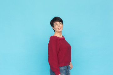 Fashion, people and style concept - Mid-aged woman in crimson sweater on blue background with copy space