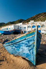 A blue boat stranded on the beach in front of the Tafelney fishing village buildings