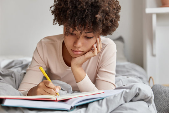 Image of beautiful woman with Afro hairstyle rewrites information in notebook from book, writes down homework, enjoys leisure time in bedroom, wears casual clothes. Female makes future plans