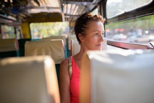 Mature beautiful Scandinavian tourist woman sitting in bus