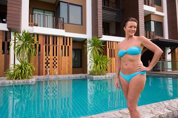 Mature beautiful Scandinavian tourist woman in bikini standing next to swimming pool
