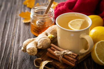 Autumn hot drink - ginger, lemon, honey tea and ingredients, wood back