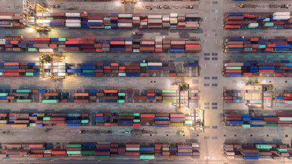Aerial view container ship from sea port warehouse with working crane bridge unloading containers shipment.