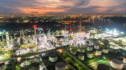 Oil refinery factory and tanker boat with beautiful sky at dusk for energy or gas industry or transportation background.