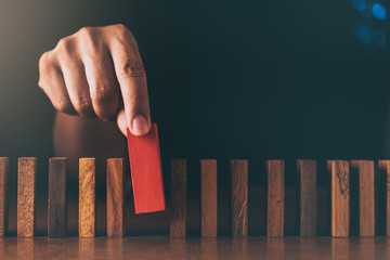 business man try to choose red color wood block from others on wooden table and black background business organization startup concept