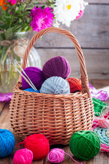 Multi-colored balls of cotton thread for crocheting in a wicker basket on a wooden table, selective focus