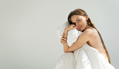 image of attractive woman holding blanket on white background