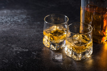 Whiskey with ice in glasses and bottle