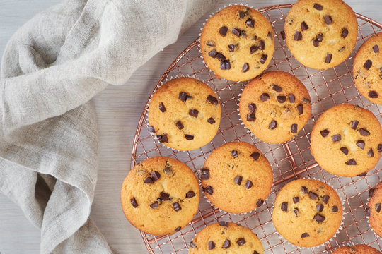 Twelve freshly baked choco chip muffins cooling off on wire mesh on wood with linen towe