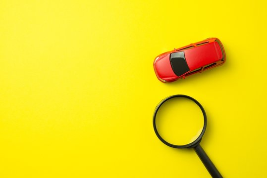 Red car and magnifying glass on yellow background with copy space. Auto insurance business concept. Cover life, property damage and injury of third party
