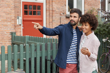 Photo of black woman and Caucasian guy have outdoor walk, stand closely, point into distance as notice friend on other side of road, use smart phone, connected to wireless internet. Livestyle concept