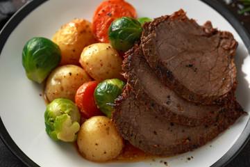Sliced Roast beef with honey glazed vegetables, served on plate. festive dinner