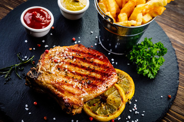 Grilled steaks with french fries served on black stone on wooden table