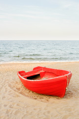 Old red boat on the beach, waves on the water and sky background