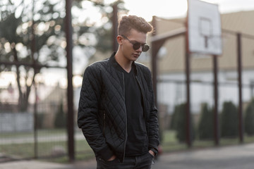 Young fashion handsome hipster man with stylish sunglasses in black trendy jacket stands in a stadium on the street
