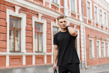 Handsome fashionable young american model man with hairstyle in black t-shirt with black bag walking on the street in the city