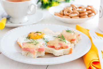 Breakfast with fried egg and hot sandwiches with sausage and cheese, horizontal