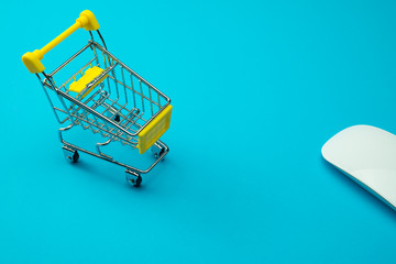 Shopping online or e-commerce modern lifestyle concept. Yellow supermarket trolley and mouse on blue background. Worldwide online shopping b2c e-commerce on internet website or social media at home.