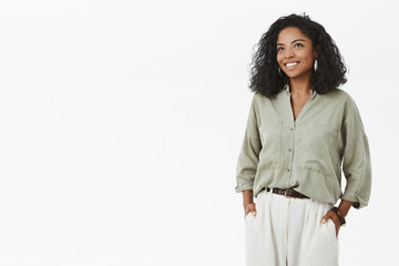 Indoor shot of successful good-looking african american female entrepreneur and mom standing in stylish hucky shirt and pants holding hands in pockets smiling happily and gazing aside