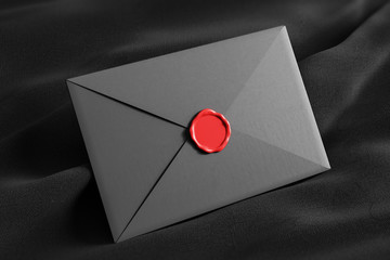 Closed gray envelope on black tissue