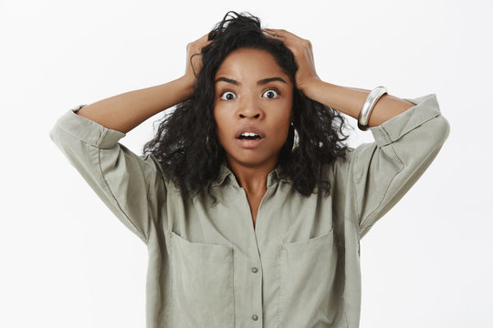 Waist-up shot of concerned girl in stupor. Portrait of shocked african american businesswoman standing anxious and shocked opening mouth holding hands on head desperate and devastated