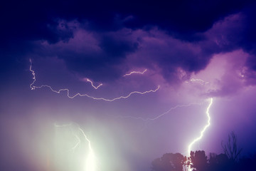 A lightning strike on the cloudy sky. Pink, lilac and purple toned image
