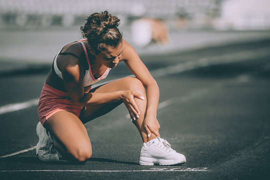 woman runner hold her injured leg on track. grey background