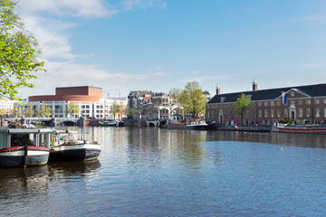 embankments of Amstel canal with traditional boats and houses in Amsterdam, Holand