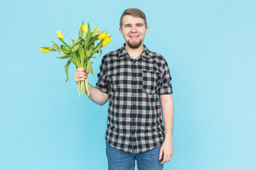 Man holding yellow tulips on blue background