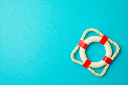 Flat lay of first aid white - red lifebuoy, lifesaver or lifebelt on blue background. Fast emergency rescue on danger catastrophe or abstract business financial economics crisis situation concept.